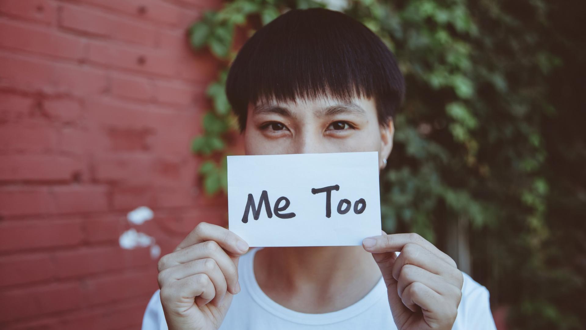 Mann asiatischer Abstammung mit weißem Shirt und MeeToo-Schild