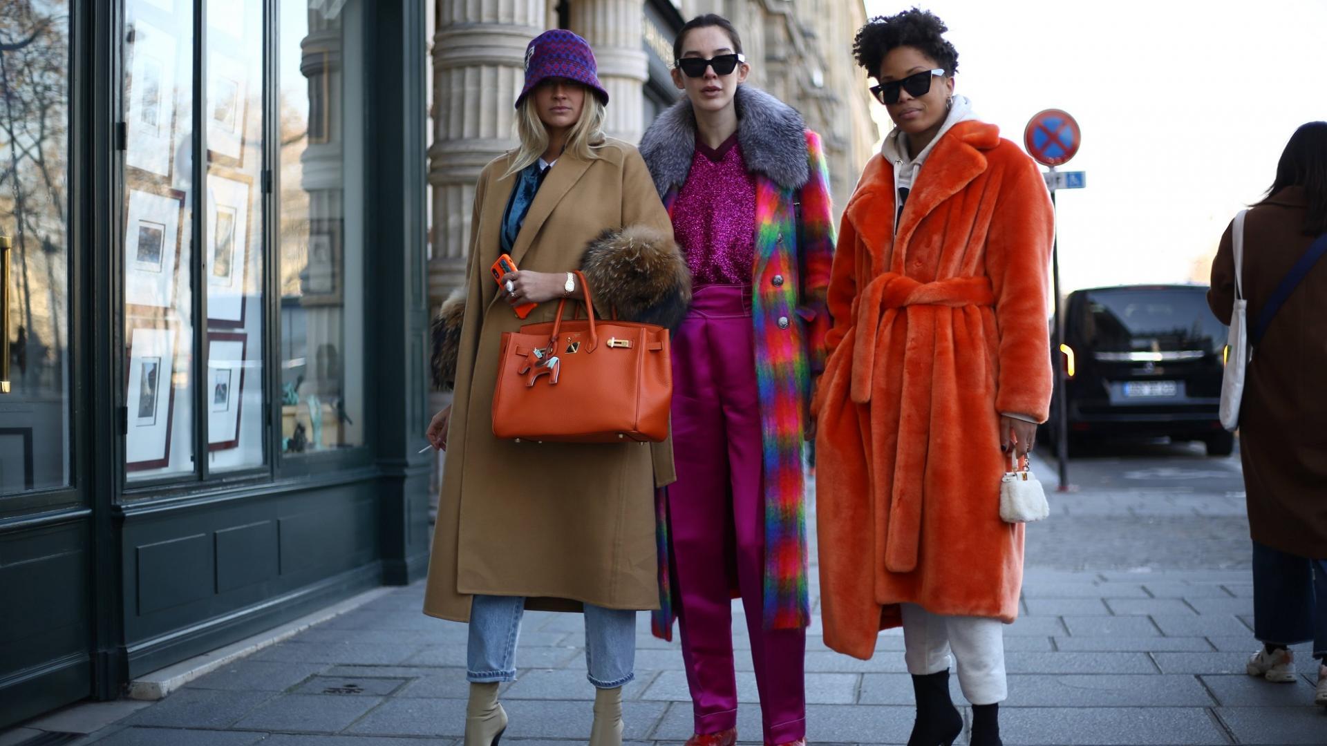 drei Frauen auf dem Bürgersteig mit modischer Kleidung und orangfarbener Hermès Tasche