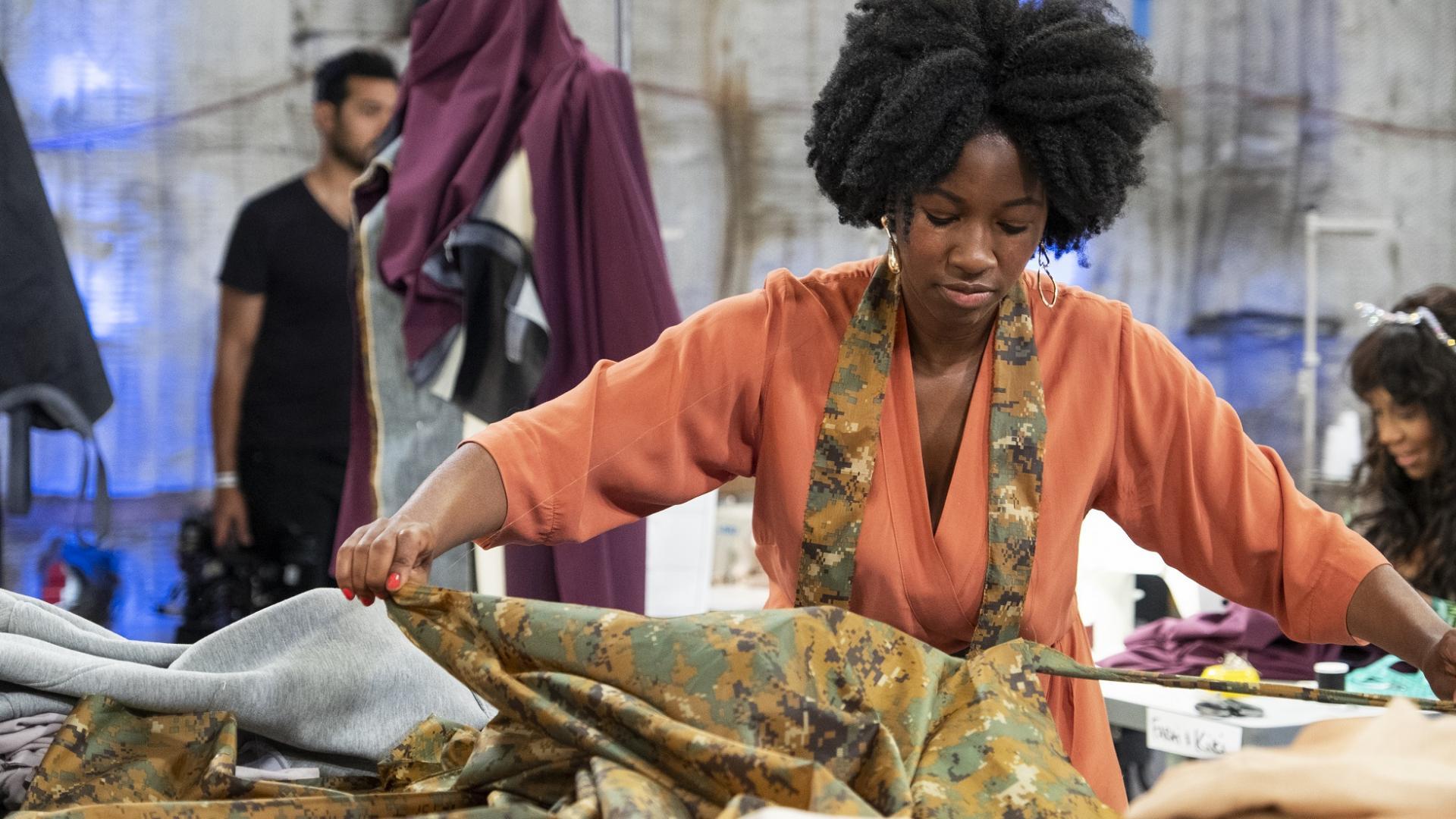 Frau mit Afrolocken und orangefarbener schneidet Stofff im Atelier