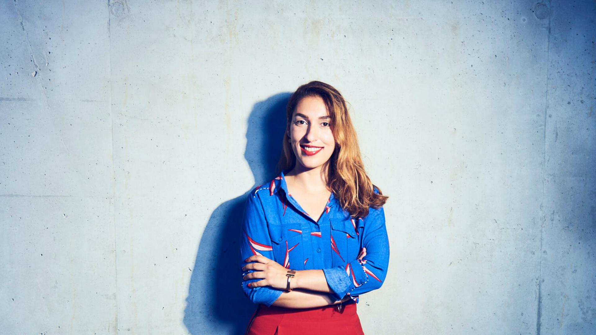lächelnde dunkelhaarige Frau mit blauem Oberteil und roter Hose vor weißer Wand