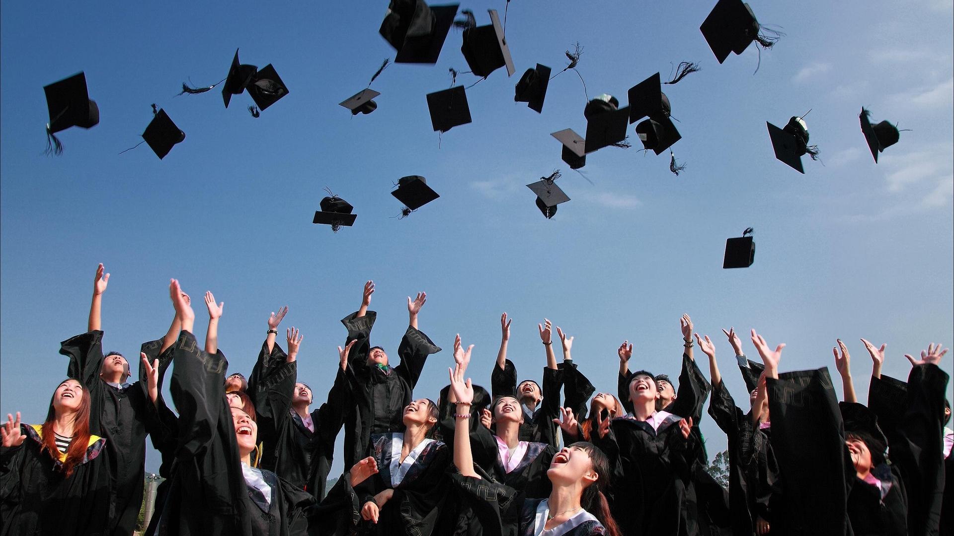 Studierende werden Unihüte in die Luft