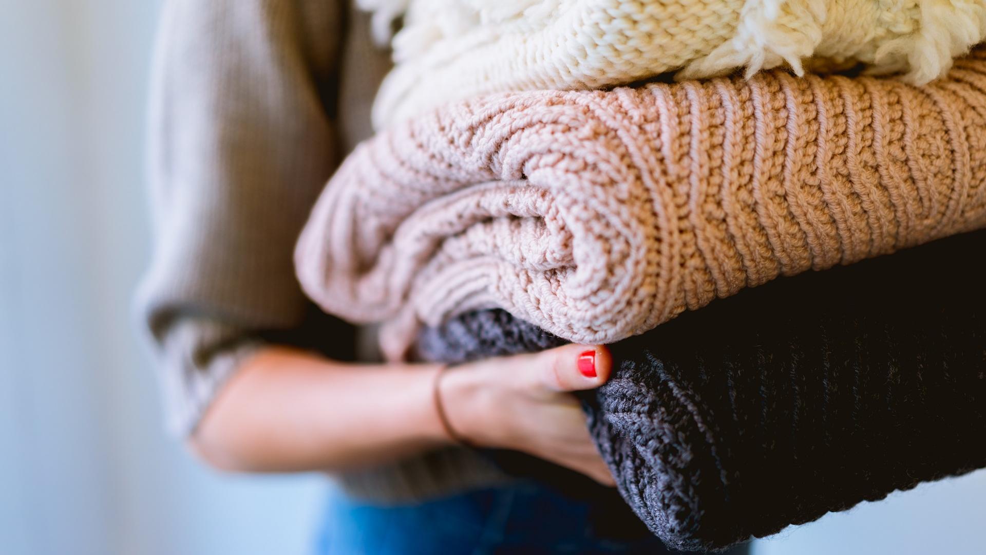 Kleider Spenden: Frau mit Pullovern