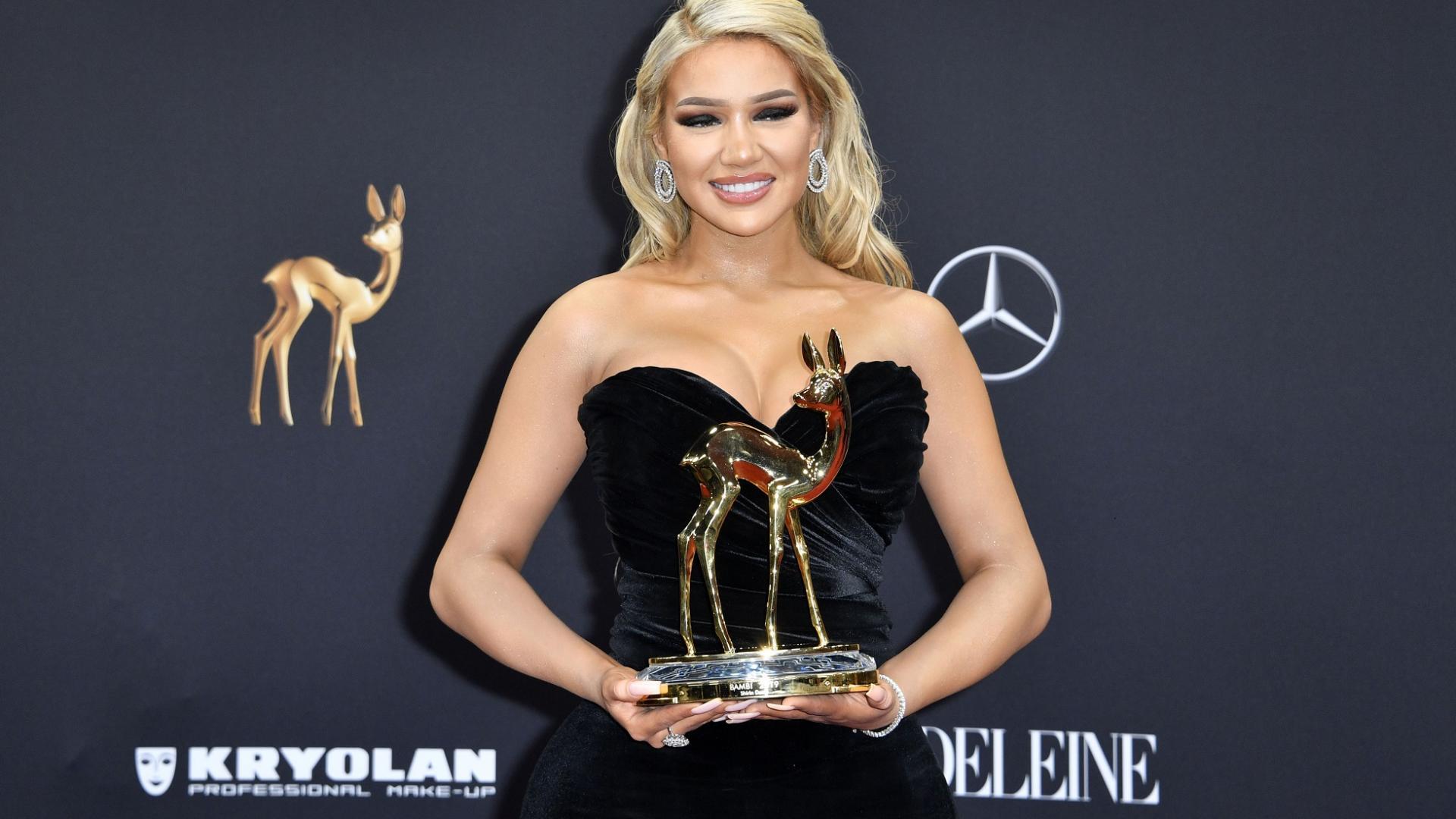 blonde Frau mit schwarzem Kleid und goldenem Bambi in der Hand