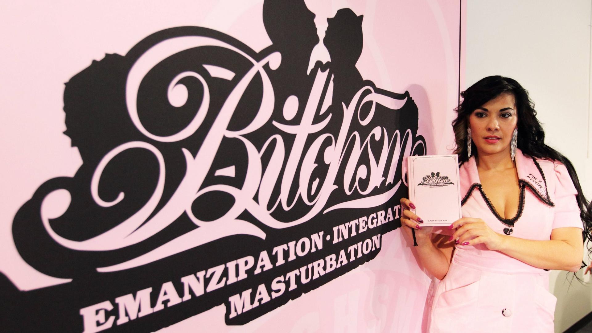 Frau mit schwarzen Haaren im rosafarbenen Kleid vor rosafarbener Wand mit rosafarbenen Buch in der Hand