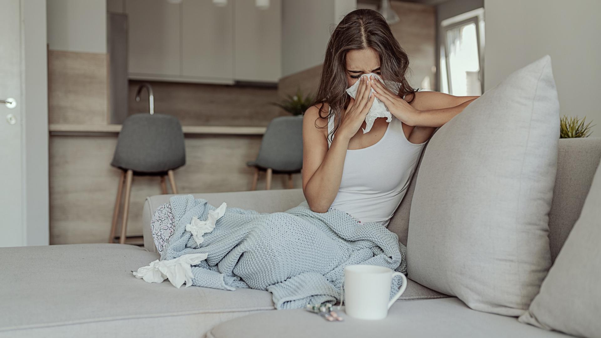 Kranke, erkältete Frau eingewickelt in einer Decke auf der Couch mit benutzten Taschentüchern
