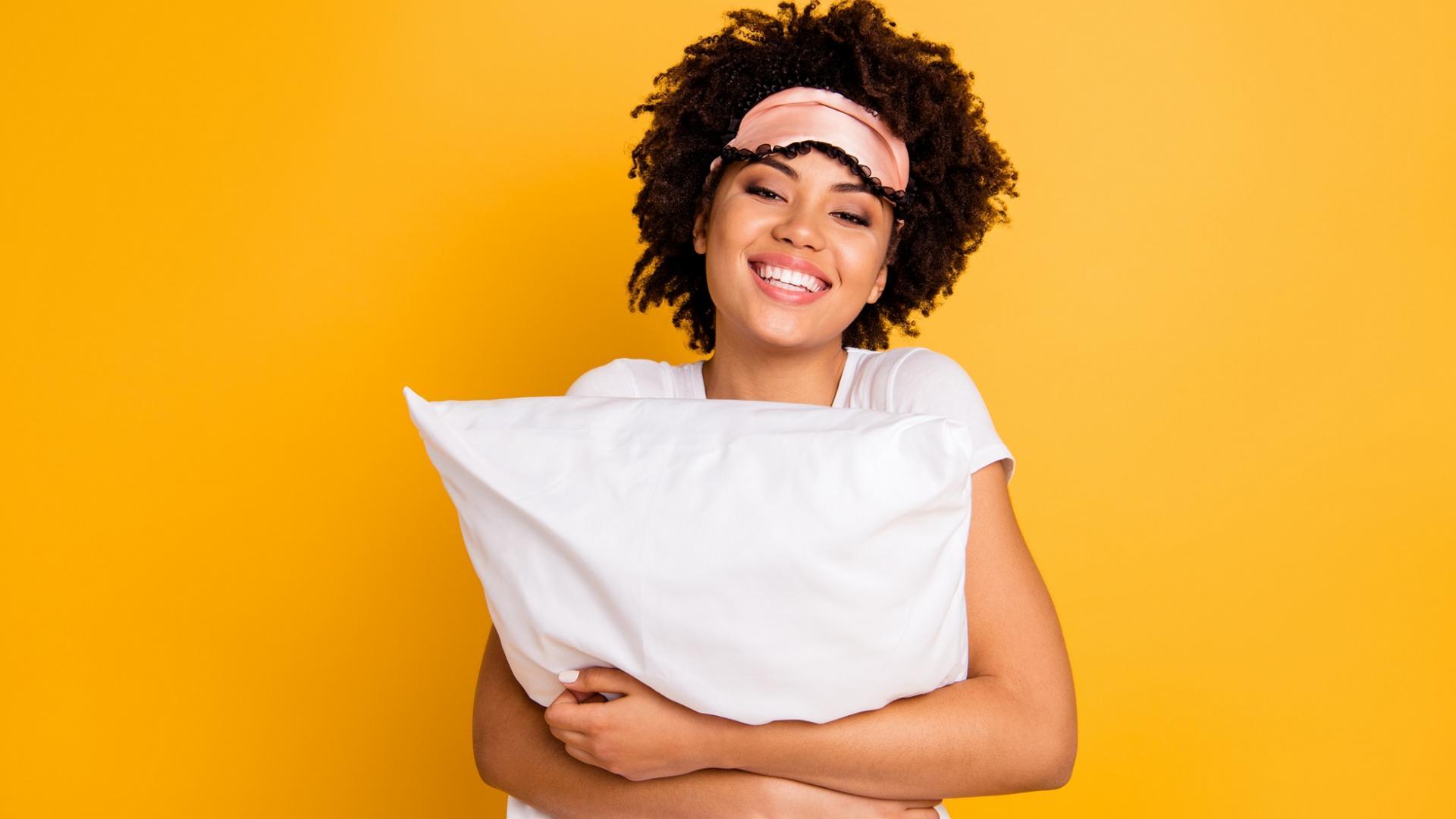 hübsche junge lächelnde Frau mit dunklen Haaren und dunkler Haut trägt Schlafmaske und hält ein Kissen in der Hand