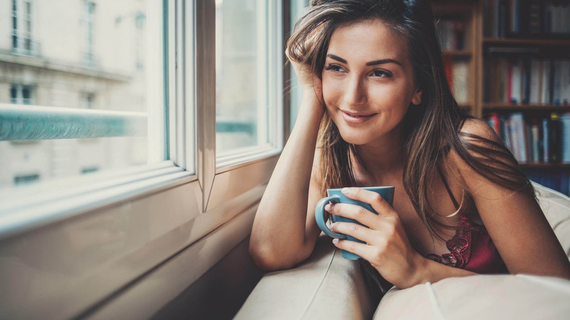 Hübsche junge Frau mit braunen Haaren hält einen Kaffeebecher in der Hand und schaut aus dem Fenster
