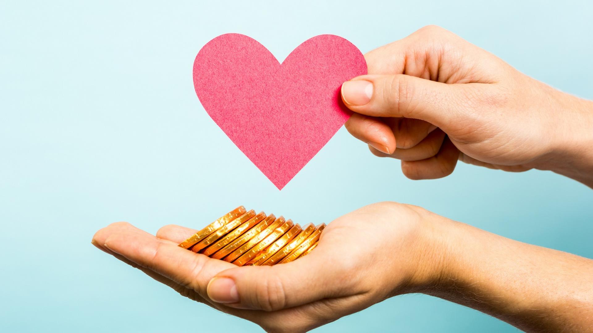 Hand mit Schokoladengeldmünzen und einem Papierherz gehalten von einer Hand vor einem hellblauen Hintergrund.
