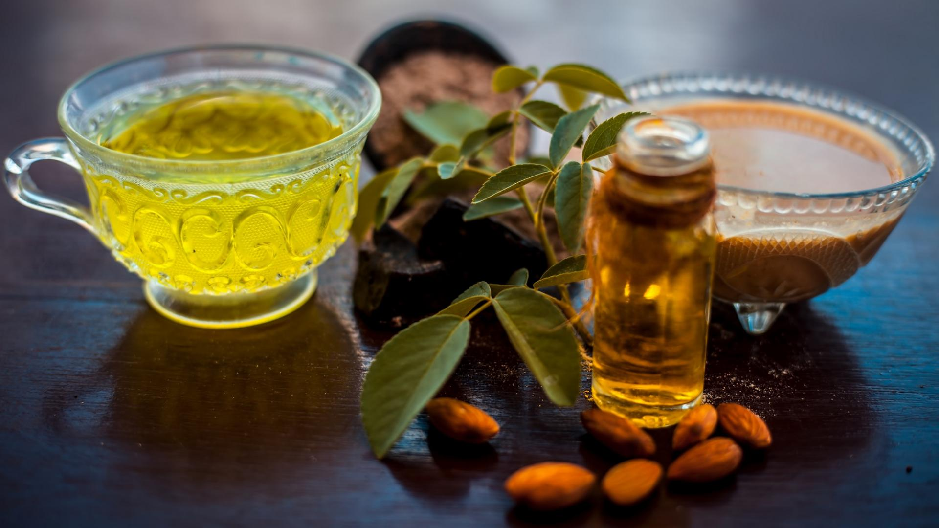 hausgemachte haarspülung auf einer Holzoberfläche: grüner tee, nussöl und kaffeee