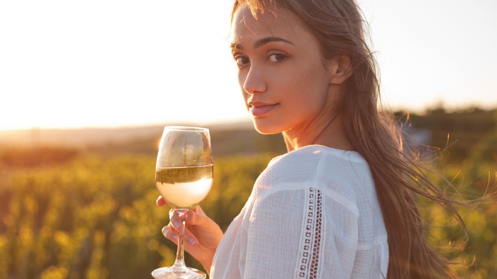 Weißwein Frau auf dem Feld mit Weißwein in der Hand.