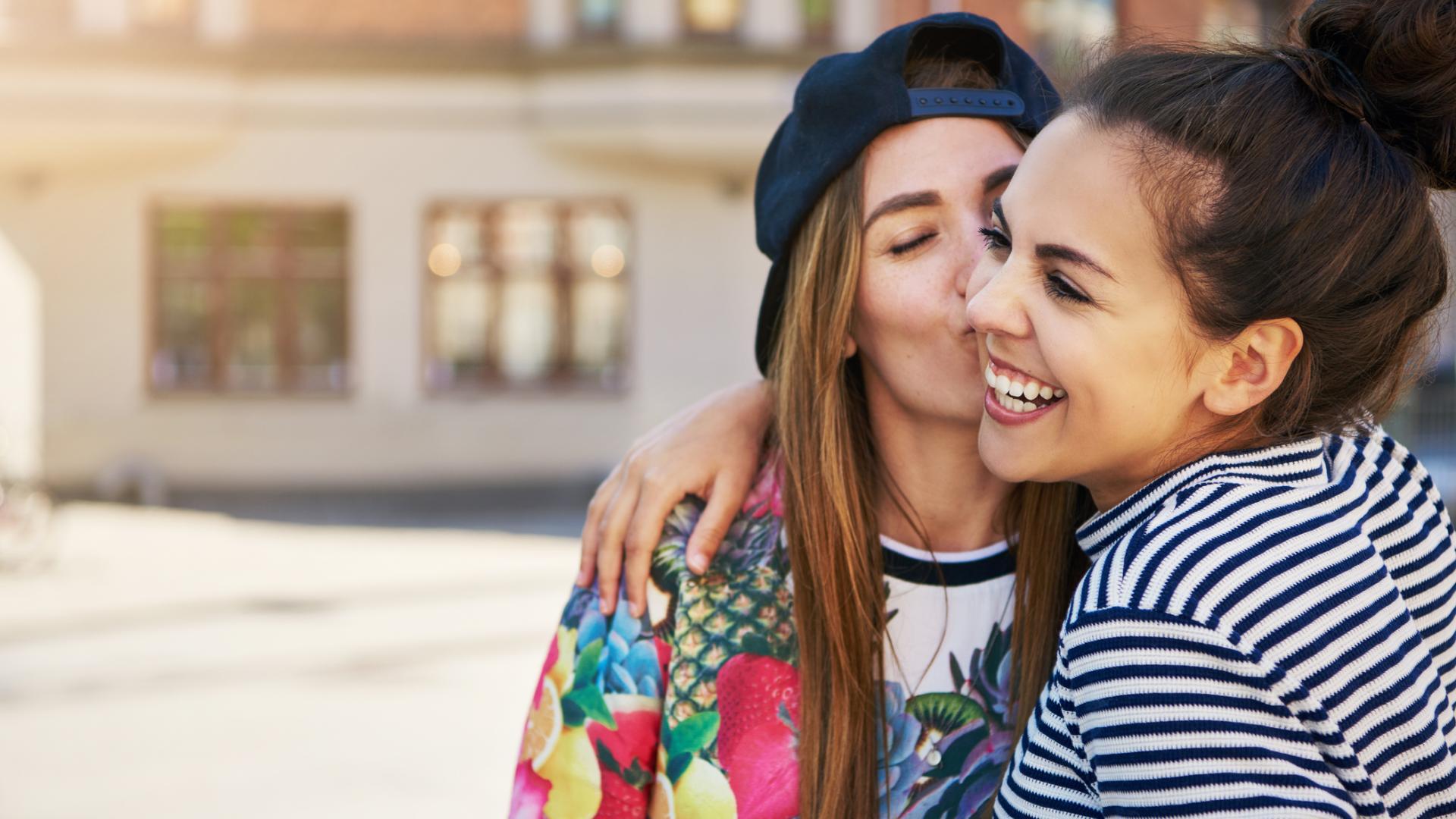 Frauen Freundinnen küssen sich auf die Wange