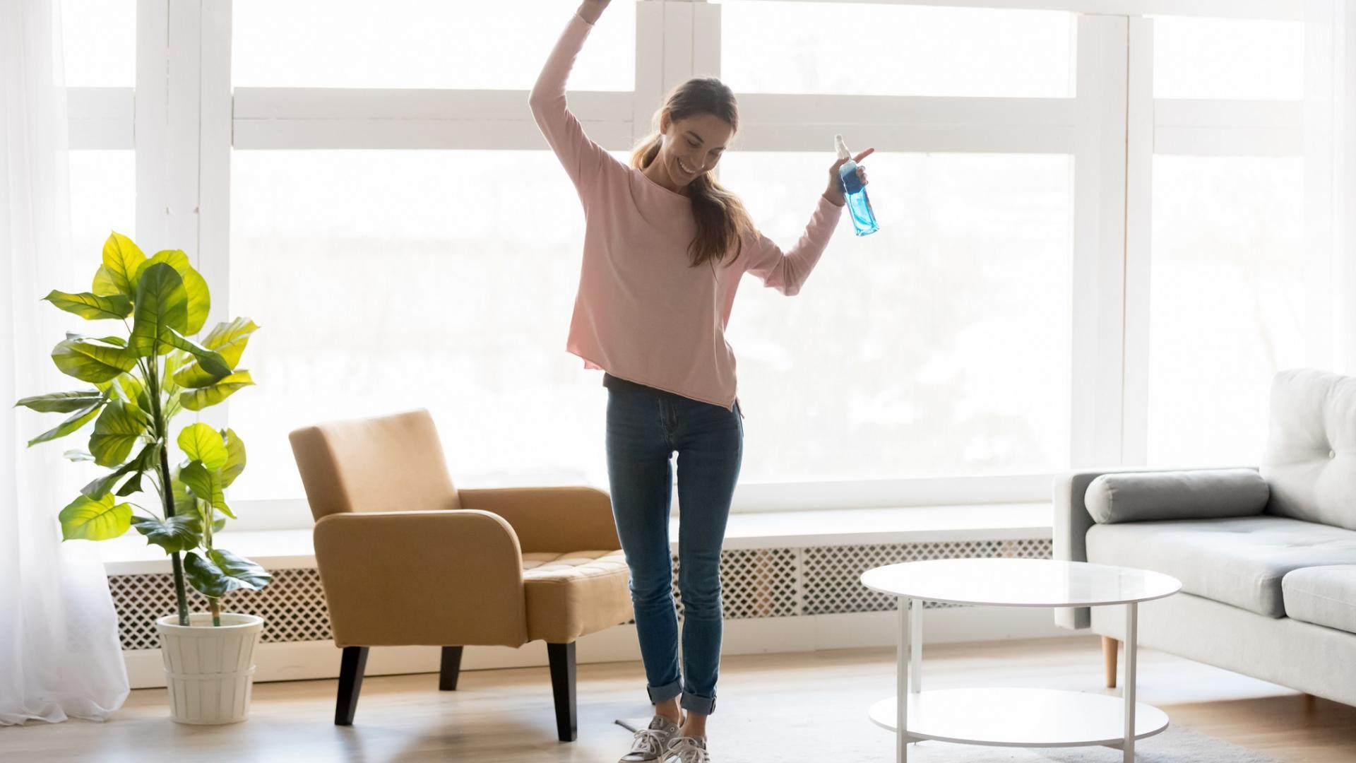 vollausgestreckte Frau in lockerer Kleidung tanzt durch die Wohnung