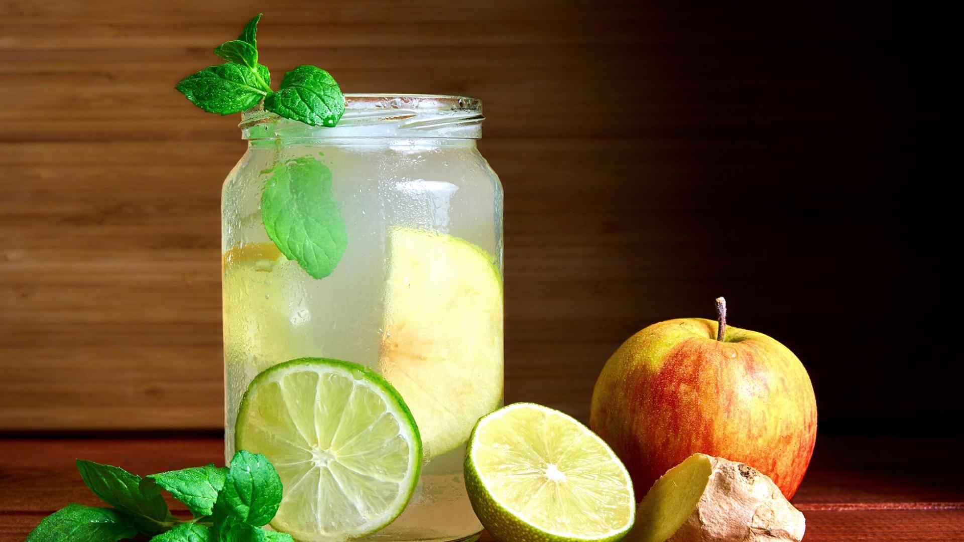 kalter hausgemachter Switchel-Drink in einem Marmeladenglas mit Limetten, Ingwer & Apfel neben dem Glas