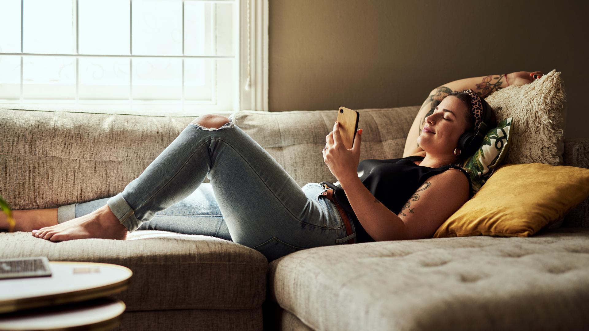 Frau entspannt am Handy liegt auf Sofa