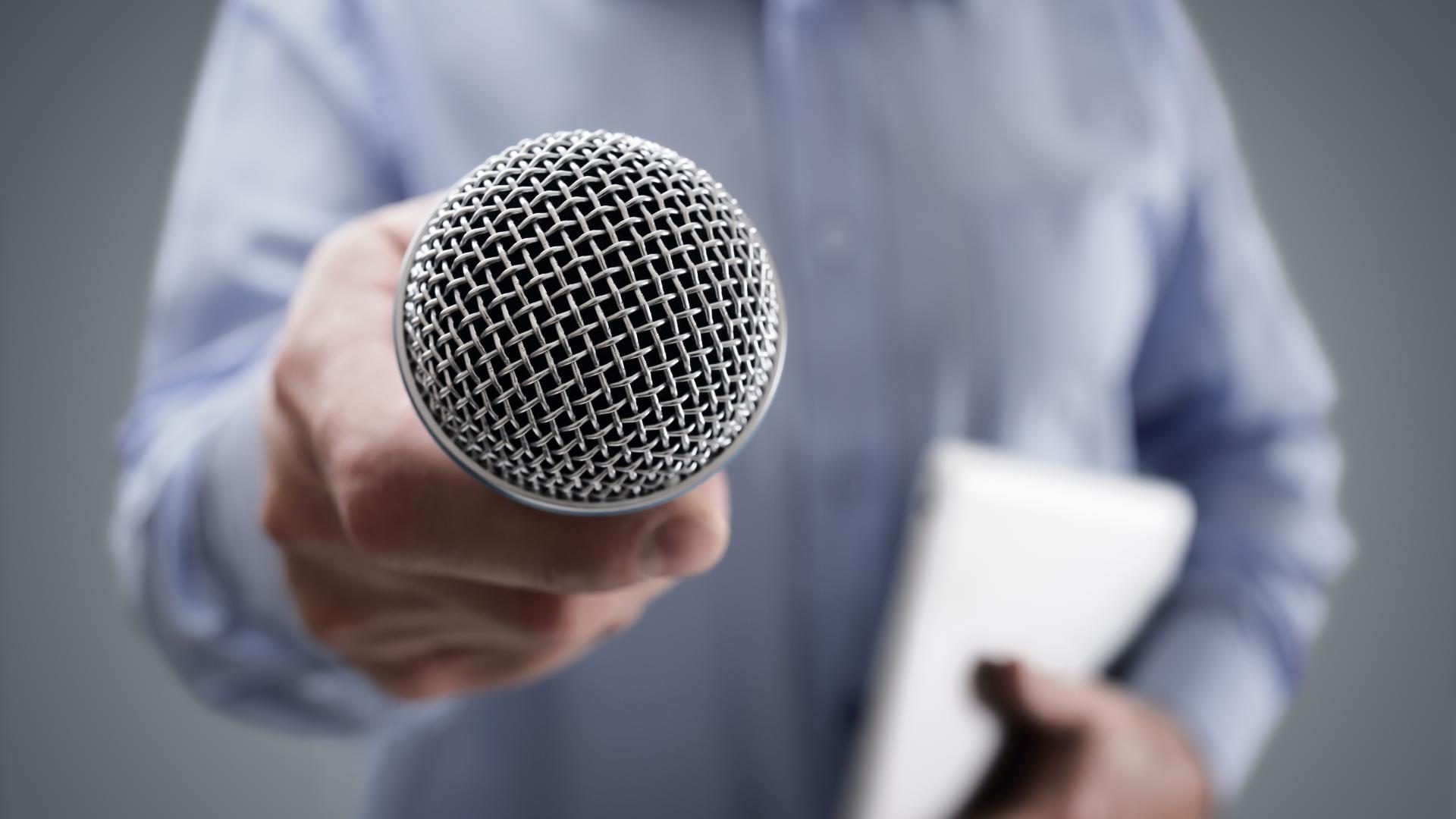 Mann hält Mikrofon in die Kamera