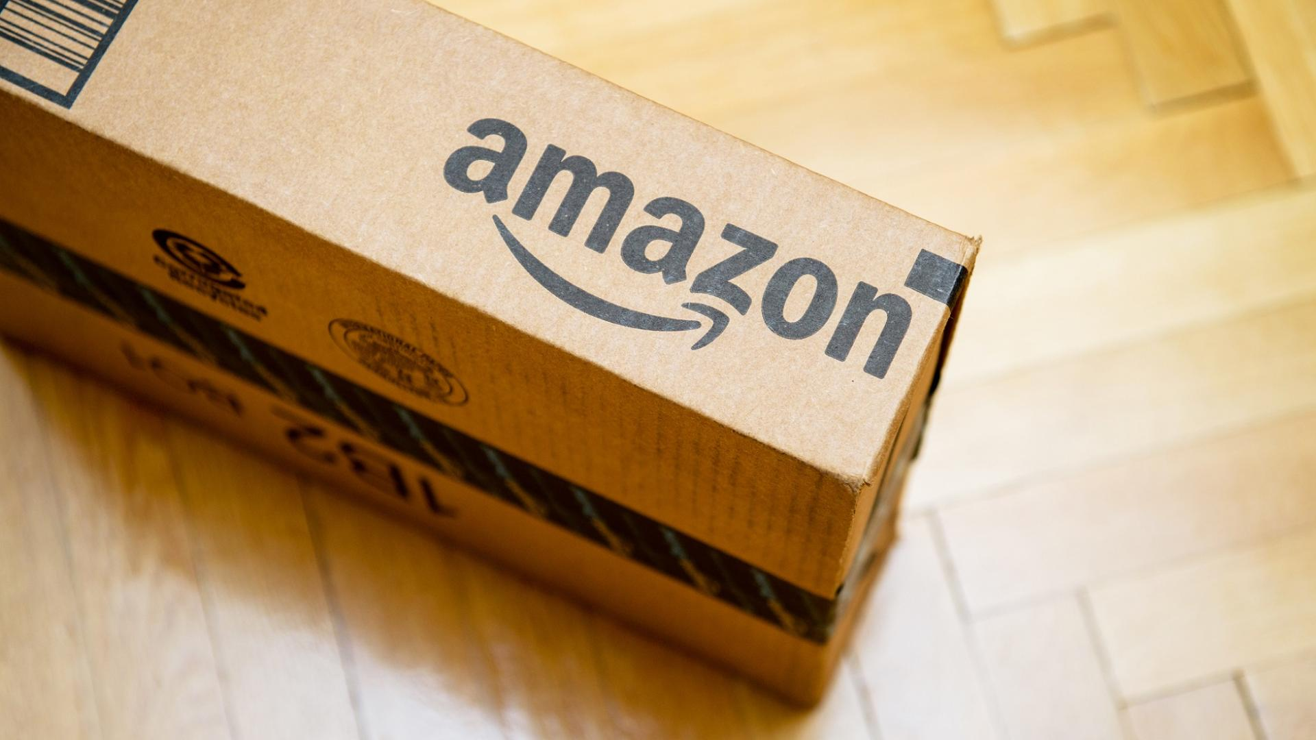 Amazon Paket mit Amazon-Logo auf dem Holzboden