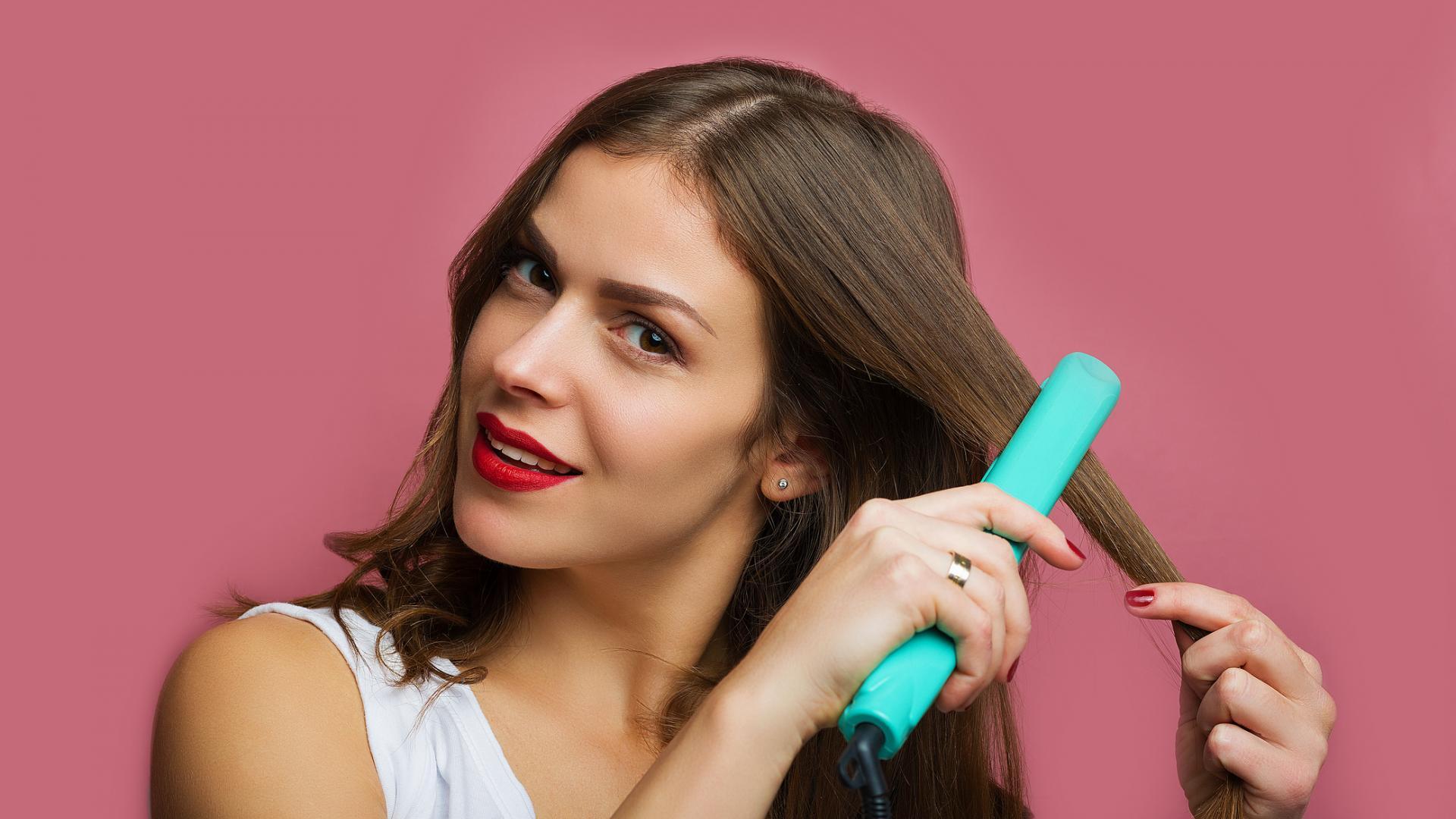 Frau glättet sich Haare vor dem schneiden