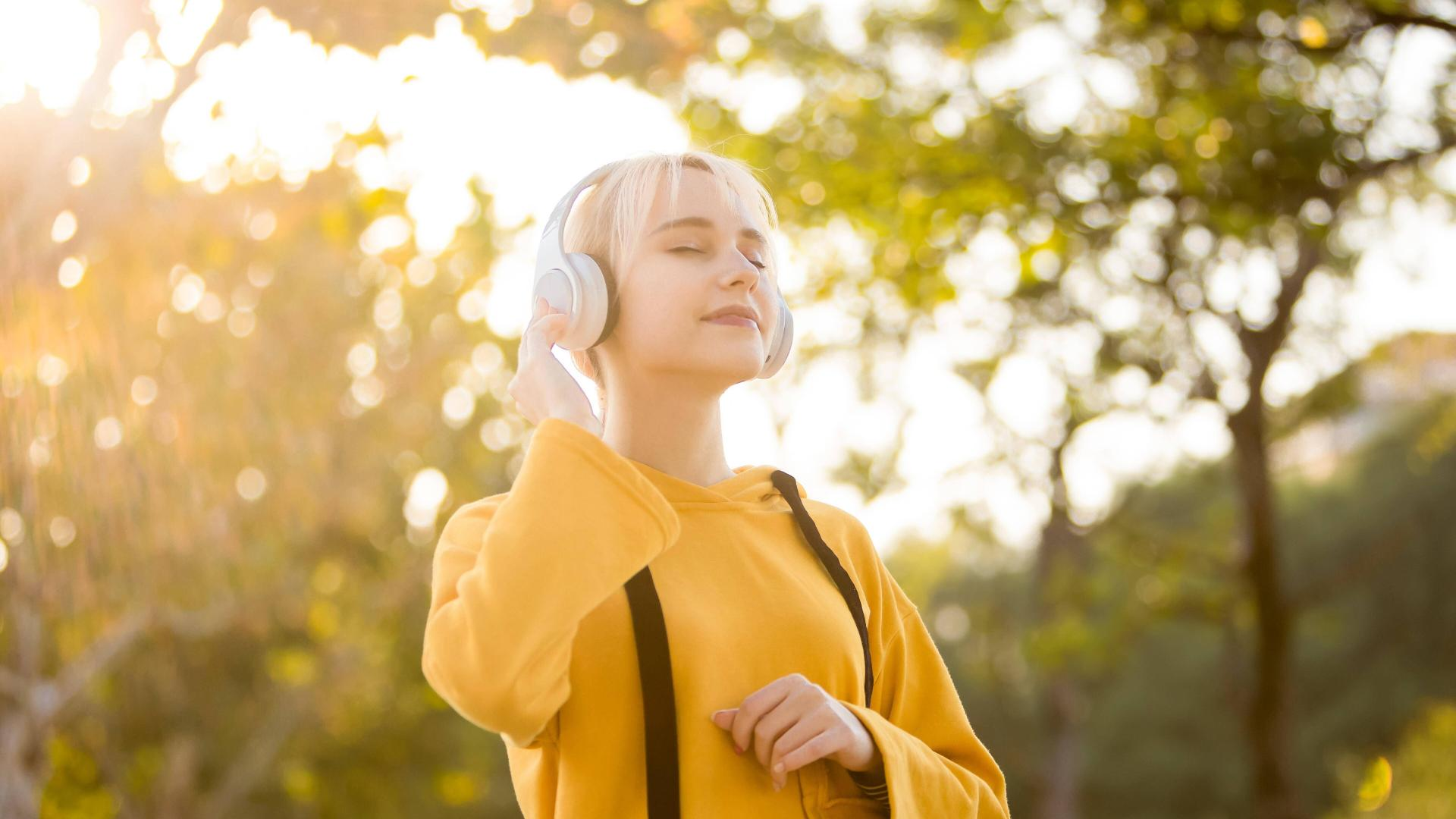 Frau hört Musik in der Sonne