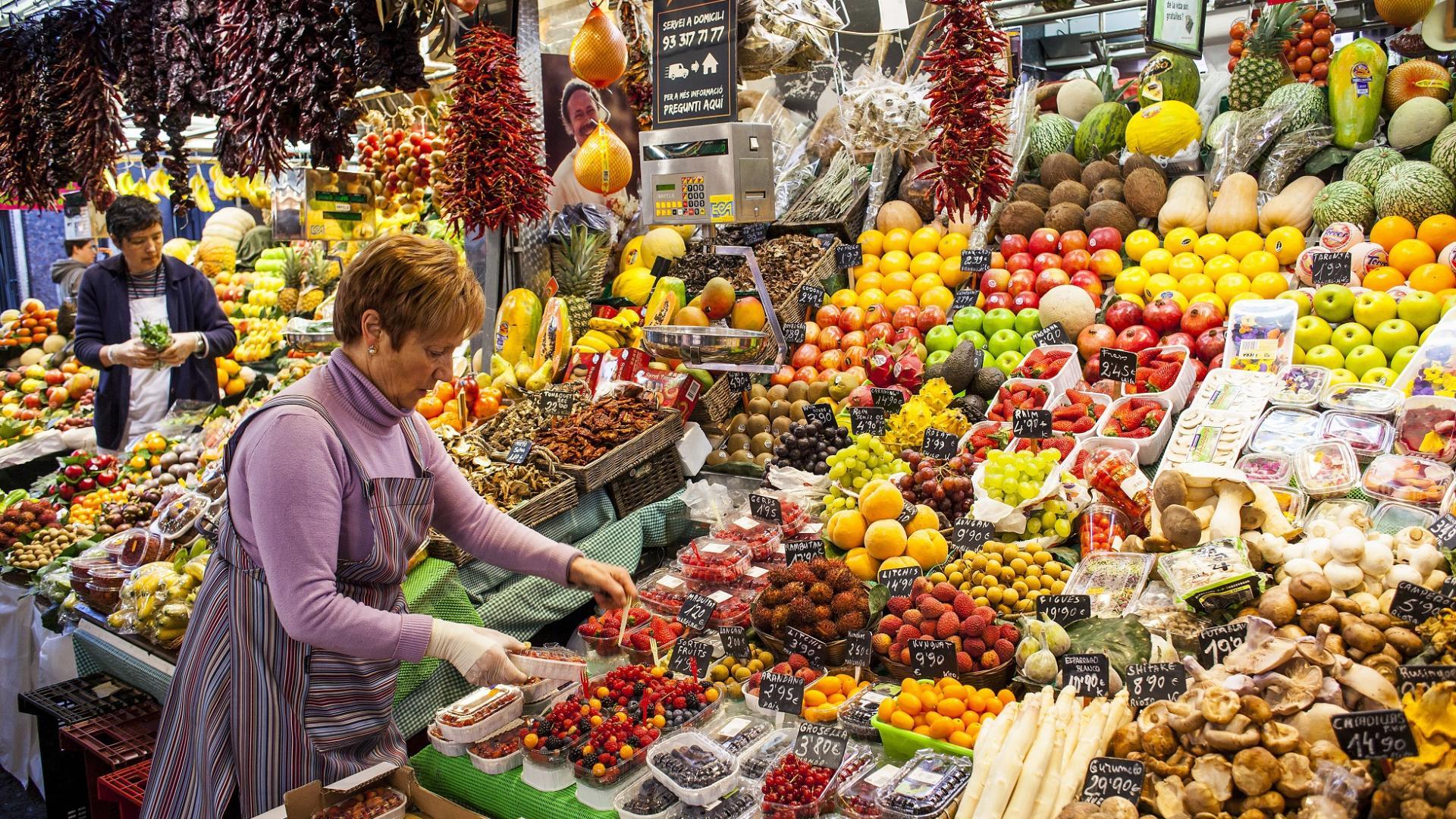 ältere Verkäuferin steht auf dem Wochenmarkt und verkauft Obst & Gemüse