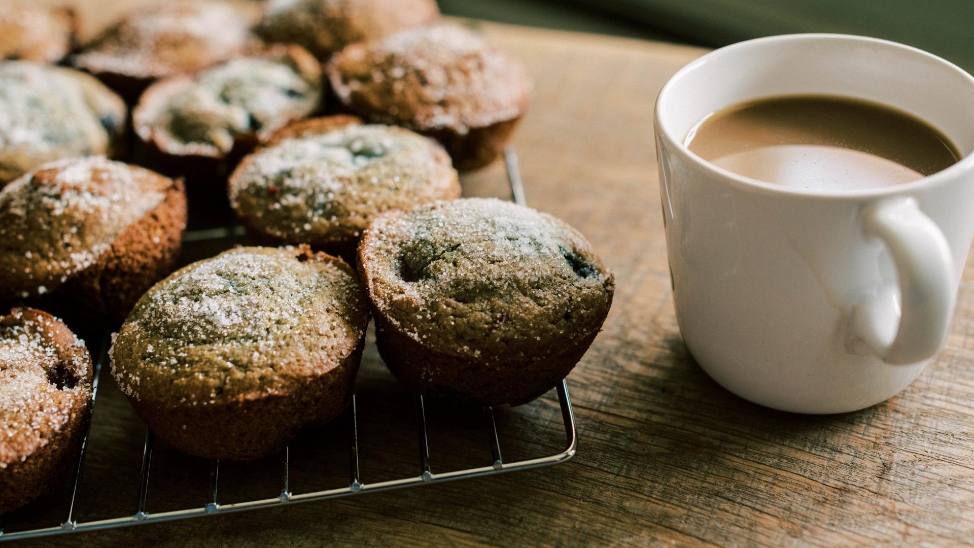 frisch gebackene Muffins mit Puderzucker auf Backgitter neben Kaffeetasse