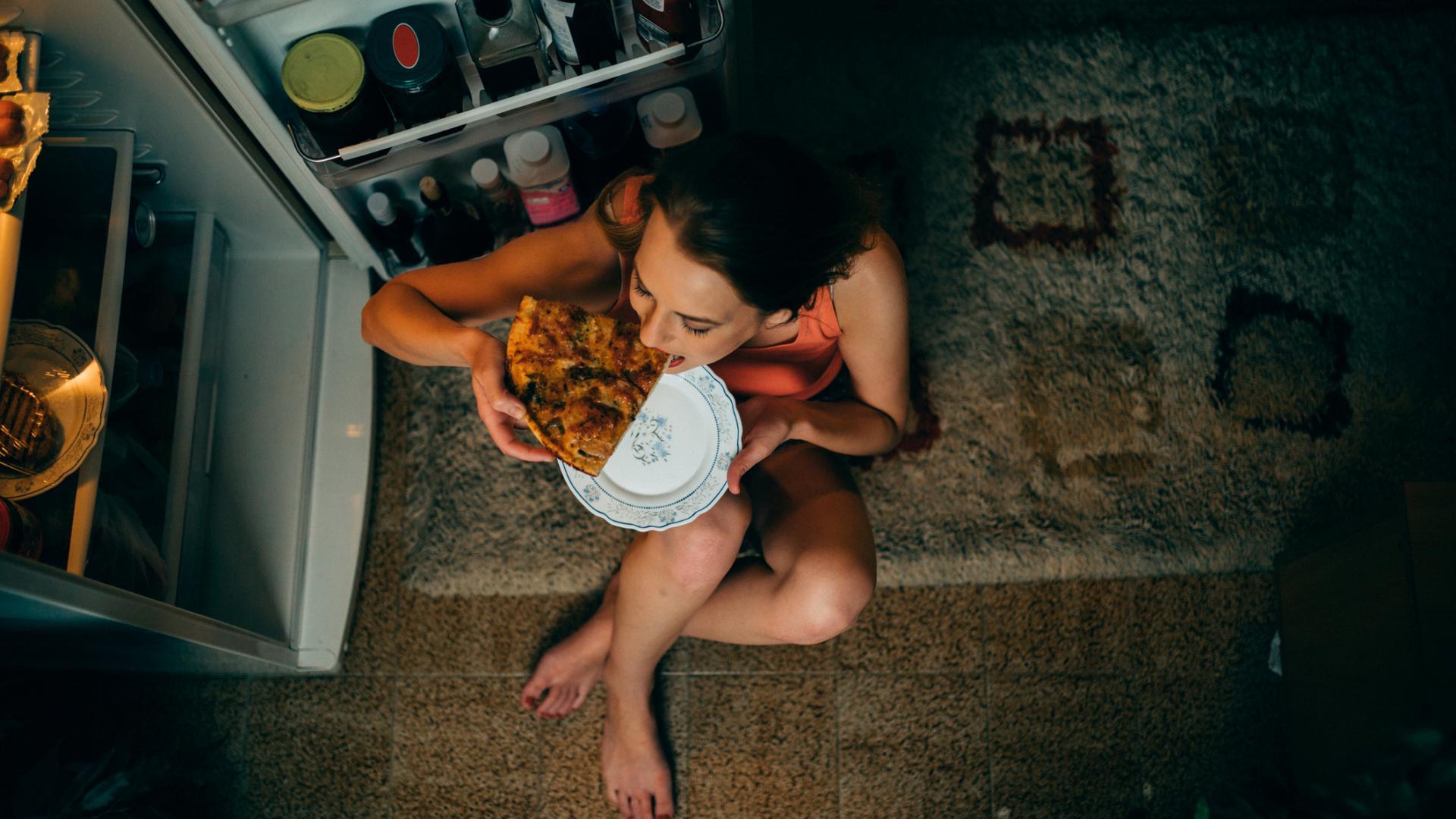 Frau snackt nachts pizza vor kühlschrank
