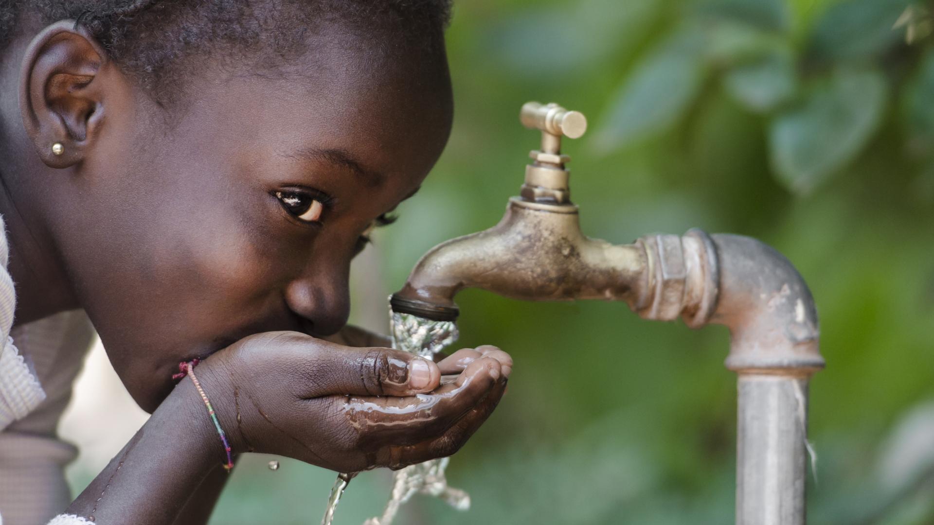 Schwarzes Kind trinkt aus Wasserhahn