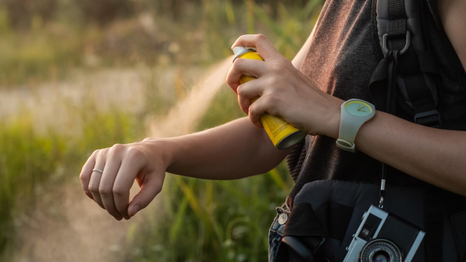 Frau sprüht sich Mückenspray auf den Arm