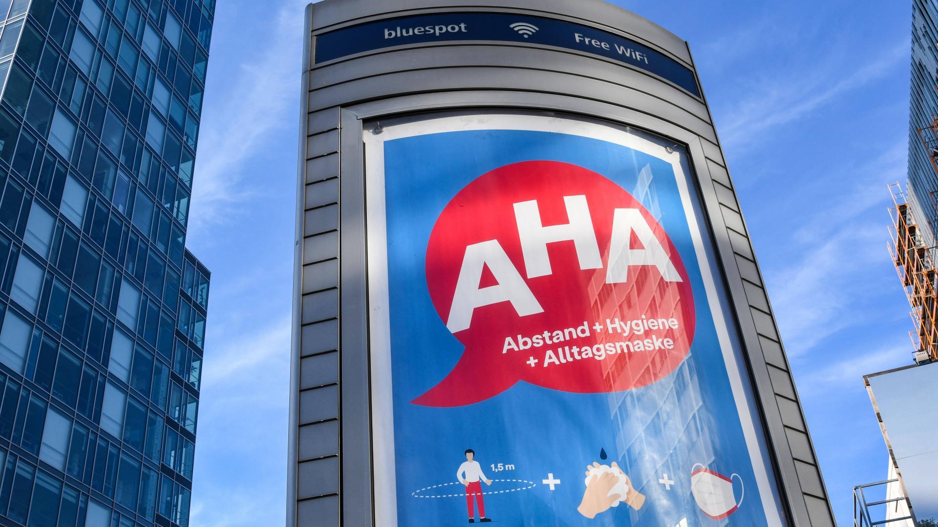 AHA- Abstand, Hygiene , Alltagsmaske- Werbung auf einer Litfasssaeule fuer die Einhaltung der Corona-Alltagasregeln. Das
