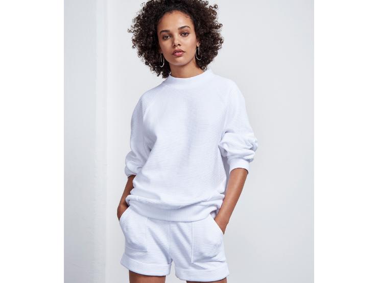Frau mit Afrolocken und weißem Pullover sowie Shorts