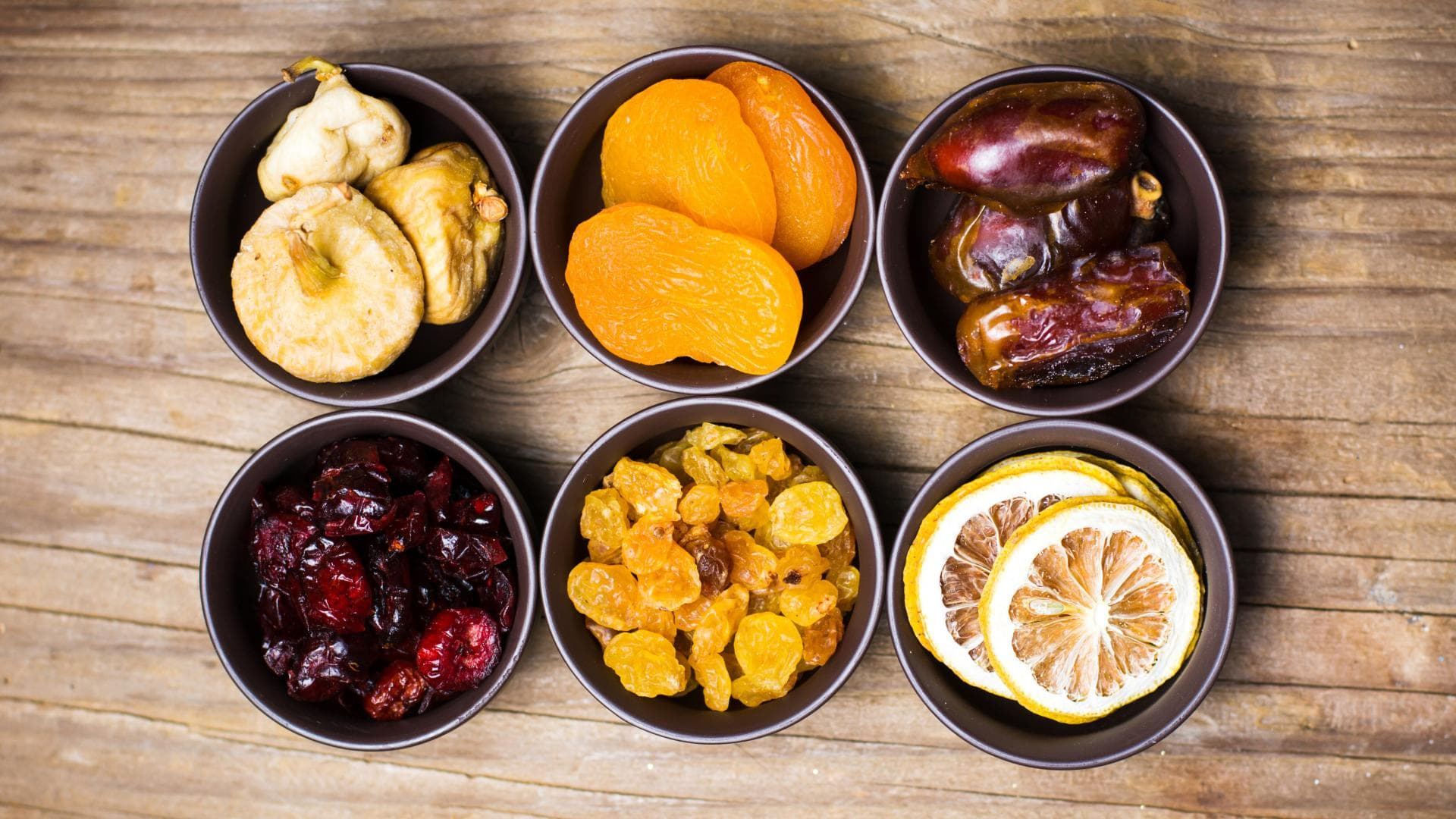 Various dried fruits in small bowls top view