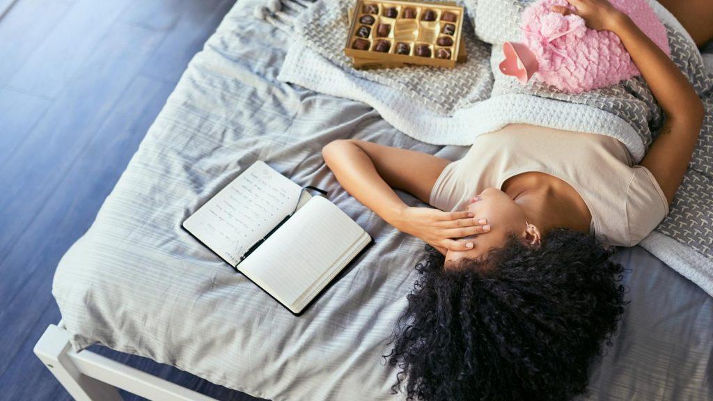 PMS lindern, Frau, schmerzen, periode, bett, wärmflasche, schokolade, schlafen, depression, traurig, zuhause, schlafzimmer, pralinen, schwarz, BIPOC,
