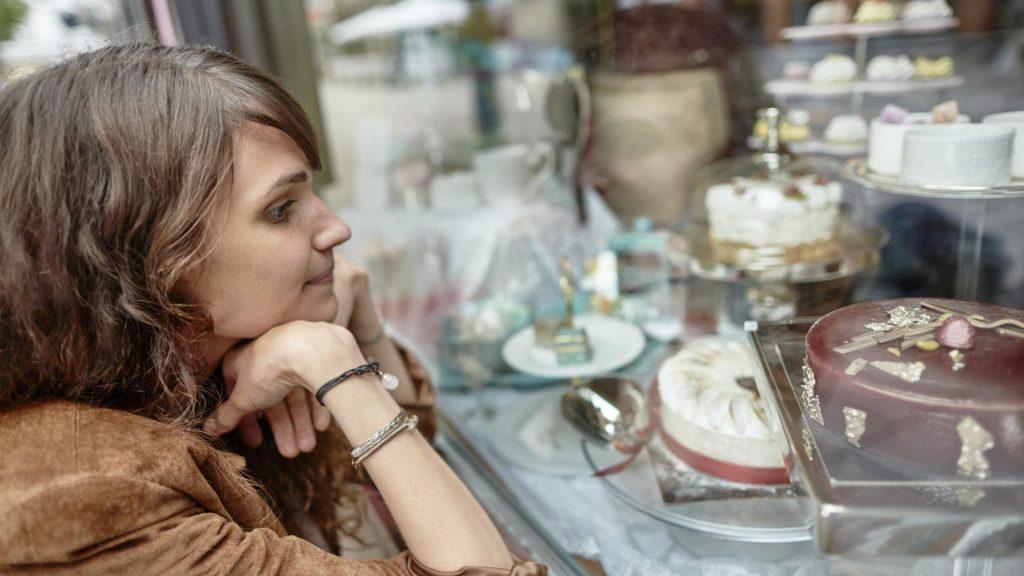 frau schaufenster torten sehnsüchtiger blick ernährung umstellen