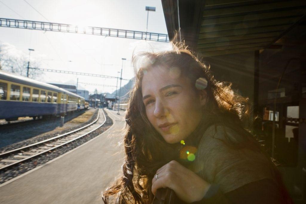Zugreisen Frau guckt aus Zug