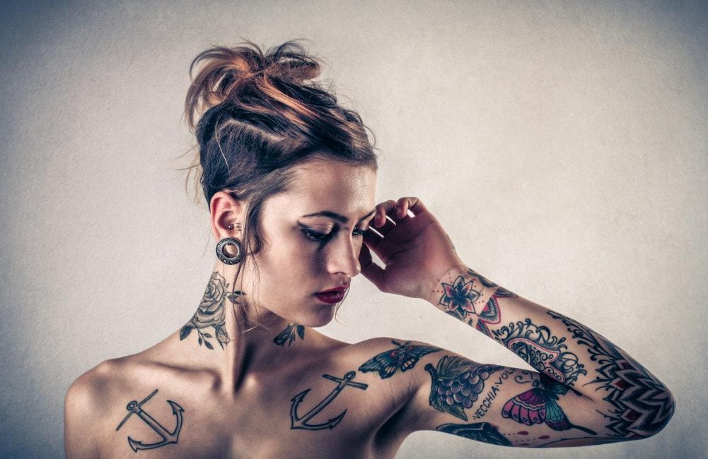 Frau zeigt ihre Tattoos auf ihrem Oberkörper.