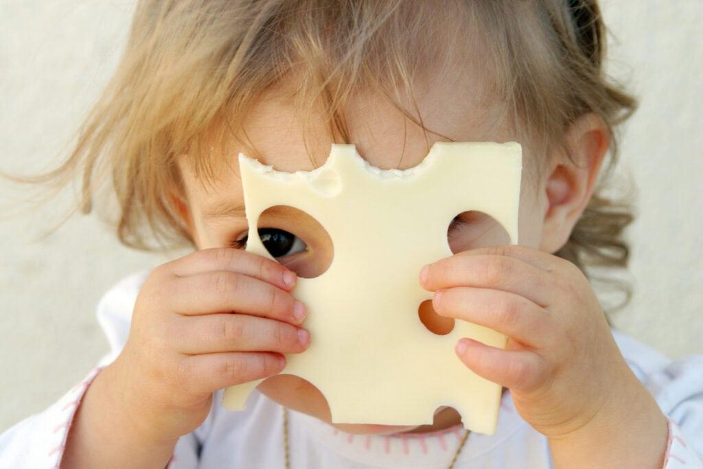Kleines Kind mit Käse vorm Gesicht