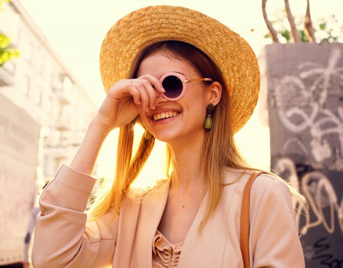 frau mit sonnenbrille und hut in der stadt sonne mineralische sonnencreme