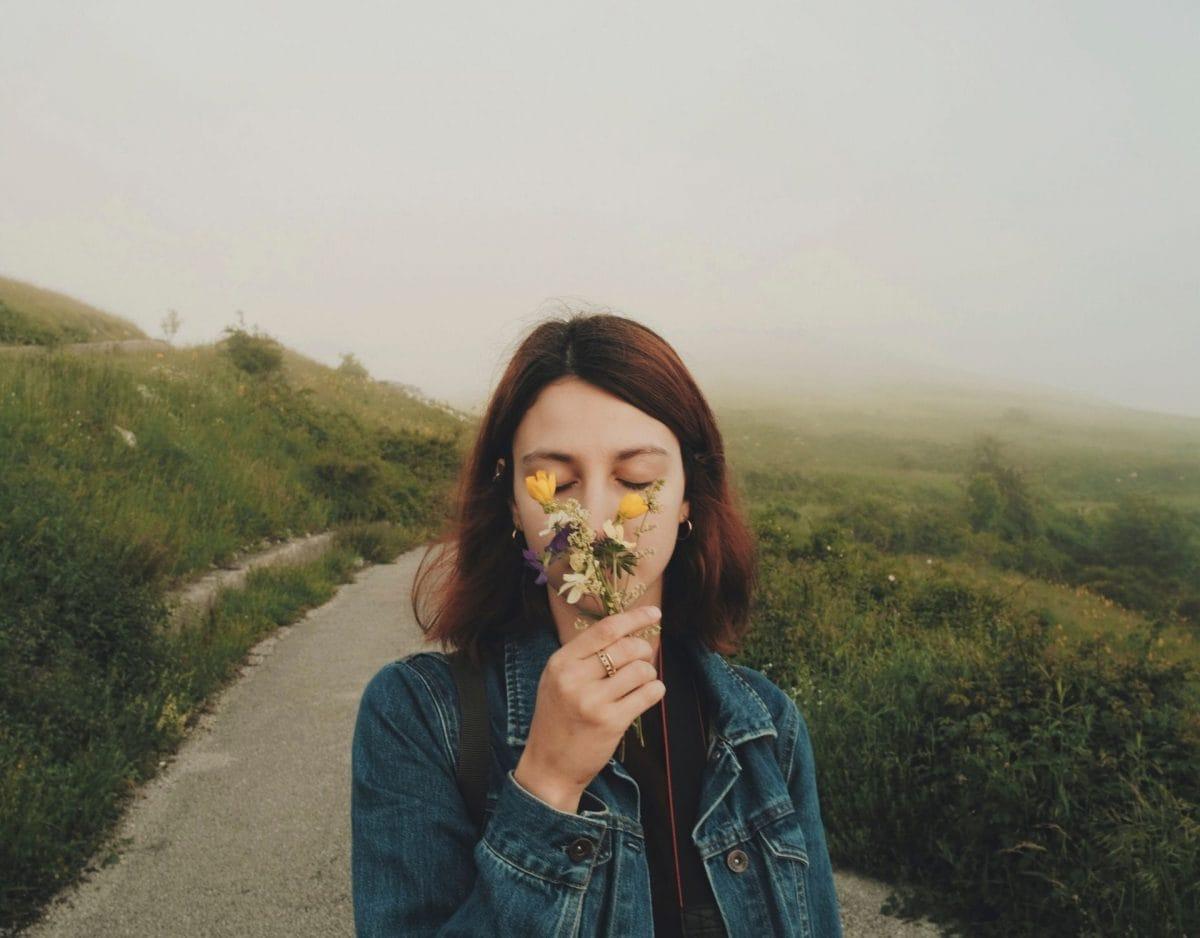 gut riechen frau auf dem feld riecht an einer blume fröhlich
