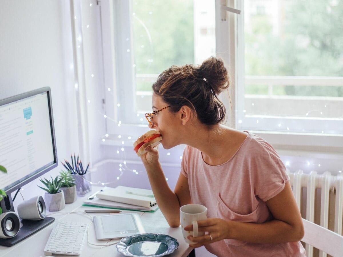 Frau isst an ihrem Arbeitsplatz
