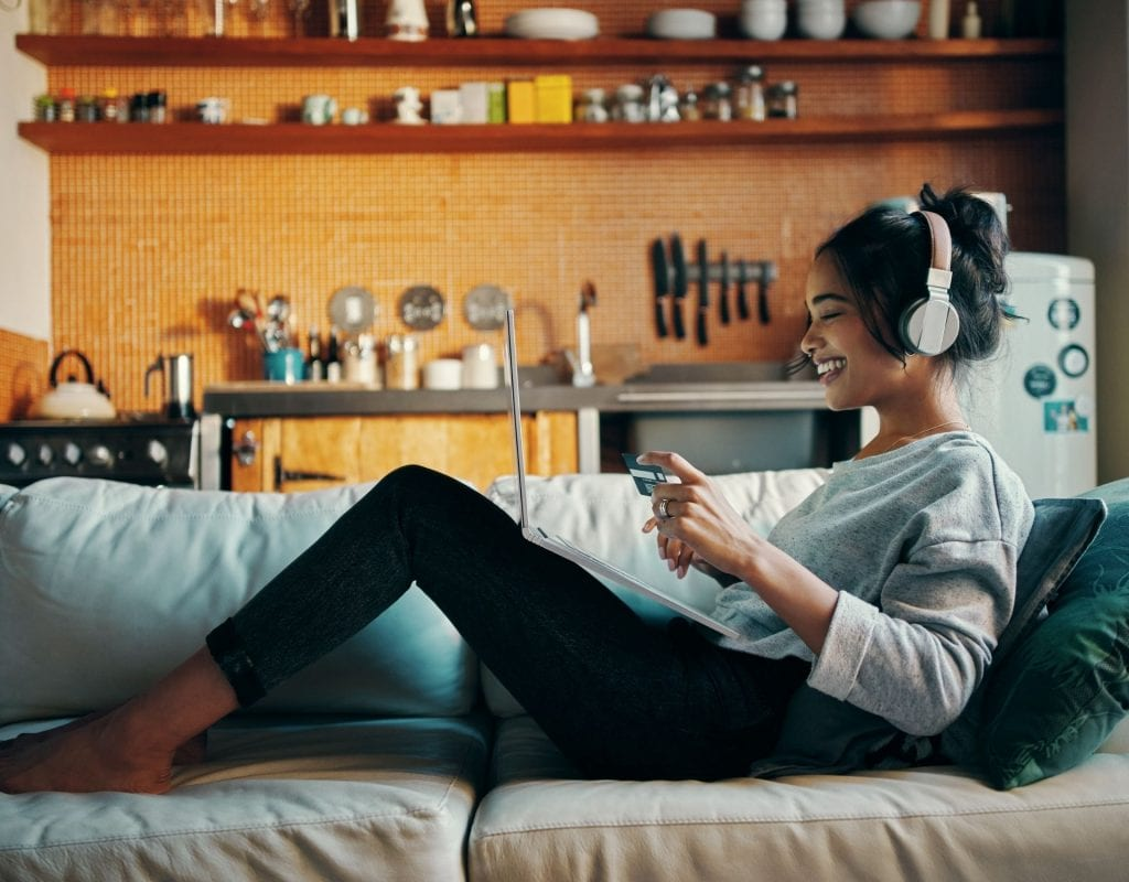 Frau sitzt lächelnd auf dem Sofa. Self Care Sunday