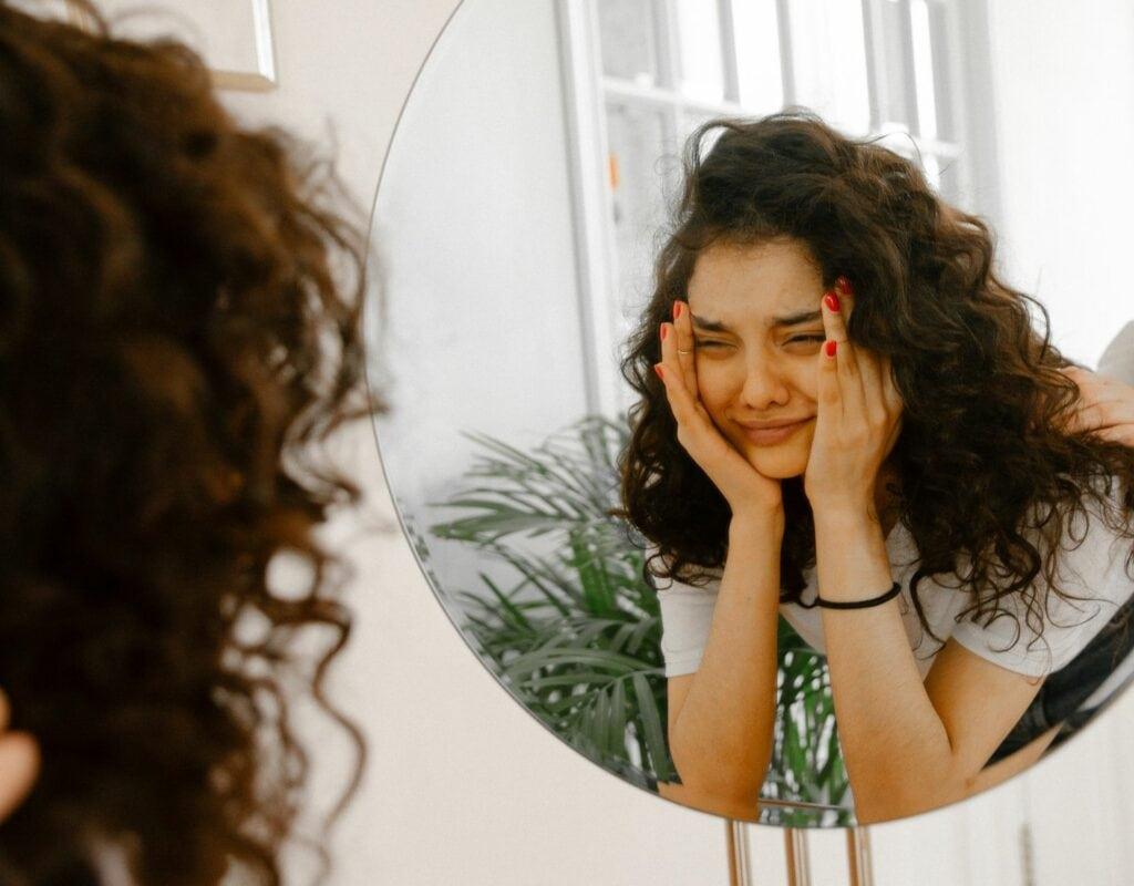 Frau schaut traurig in den Spiegel