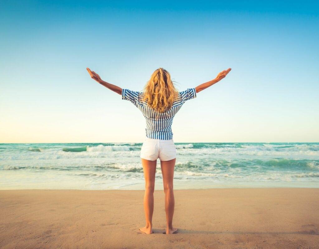 Frau am Strand mit den Armen in der Luft