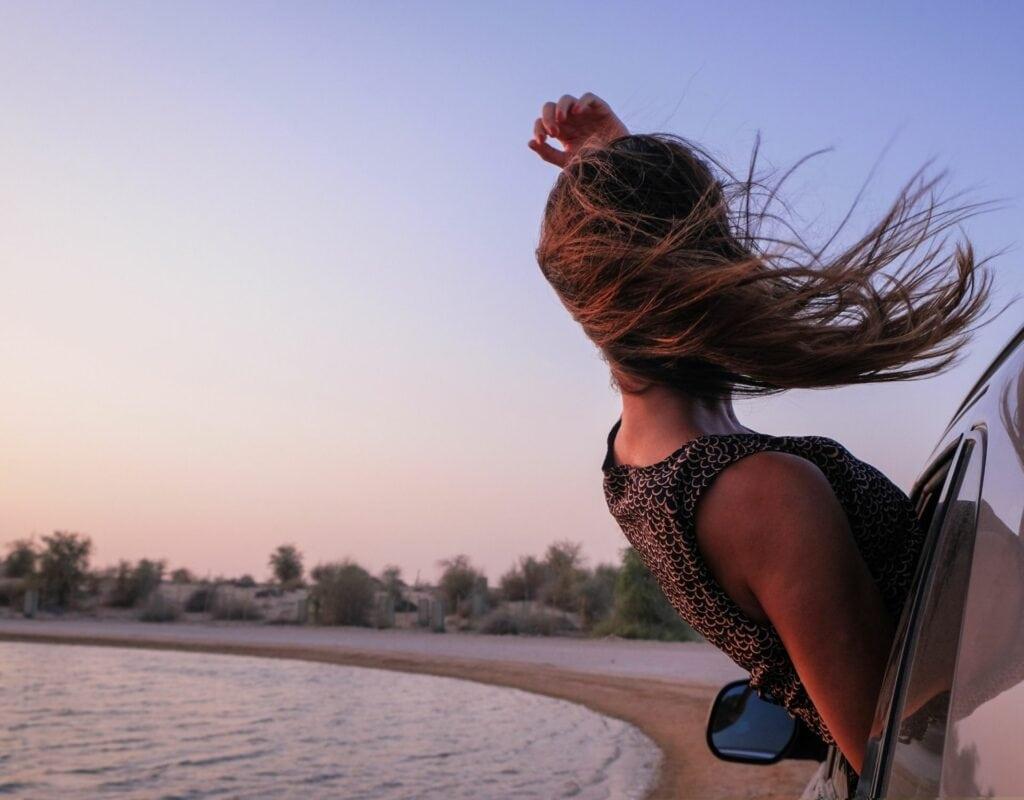 Frau im Auto während des Sonnenuntergangs. Selbstliebeübungen