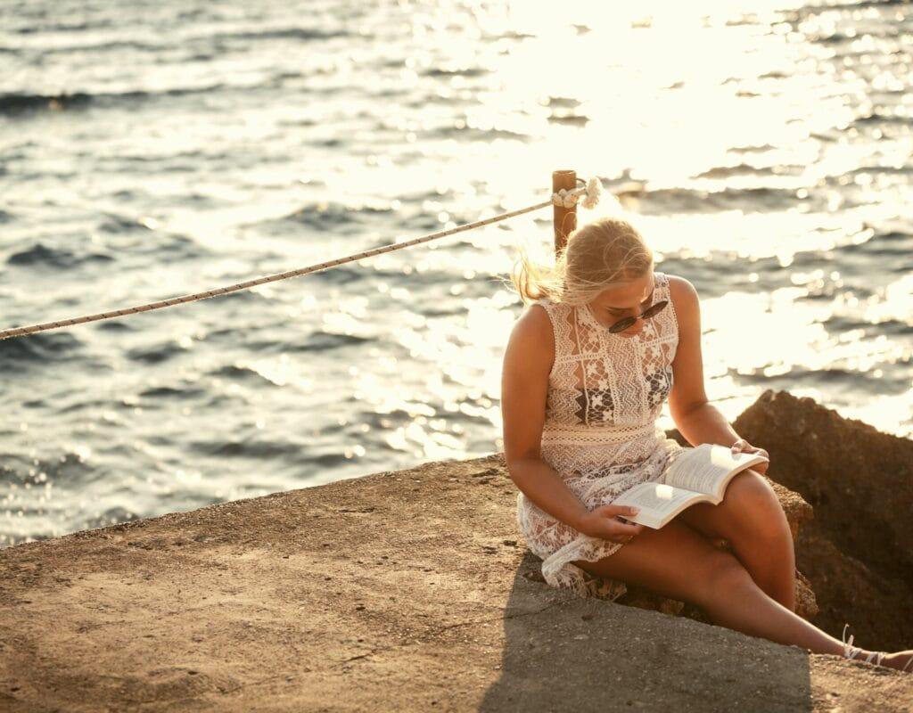 Frau liest am Meer ein Buch