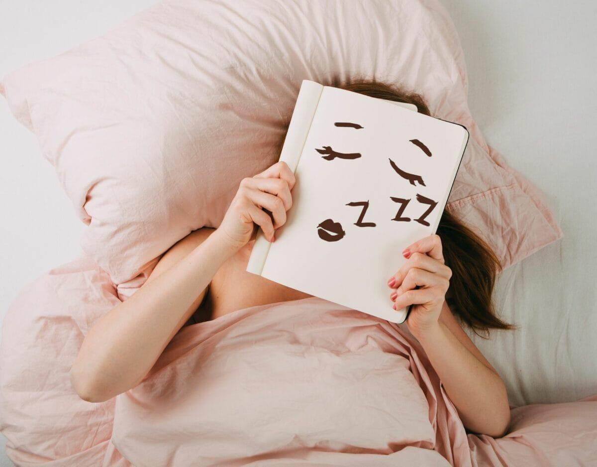 Frau im Bett mit Block vor dem Gesicht