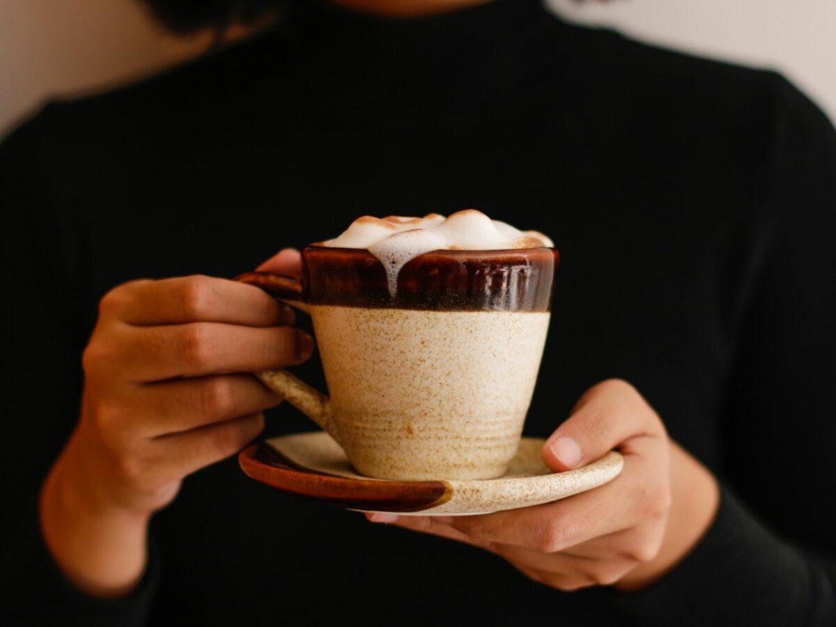 Frau hält Kaffee in der Hand