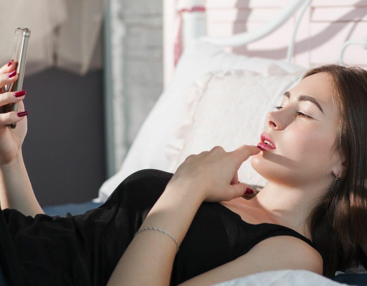 Frau am Handy im Bett, nachdenklich oder erregt