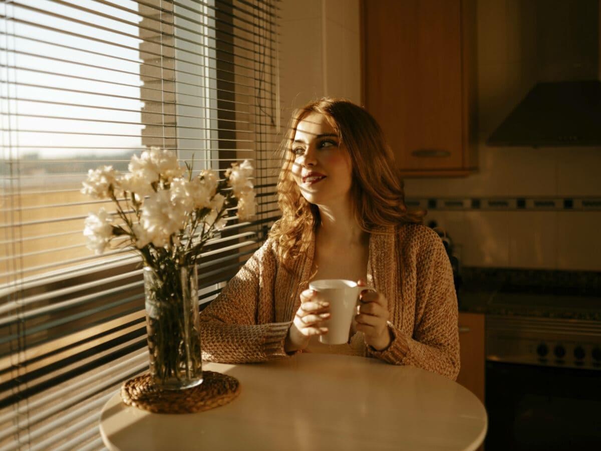 Frau am Tisch mit Kaffee in der Hand