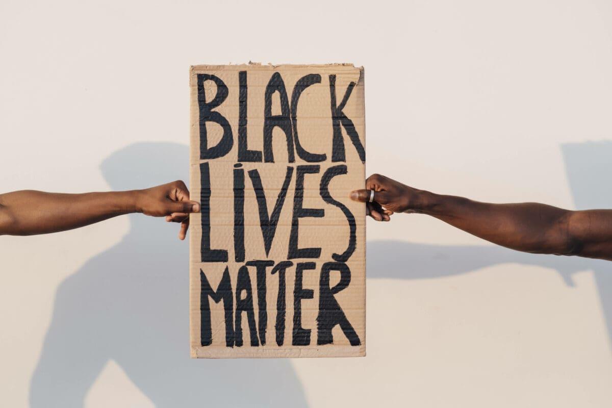 Zwei Schwarze halten BLM Schild