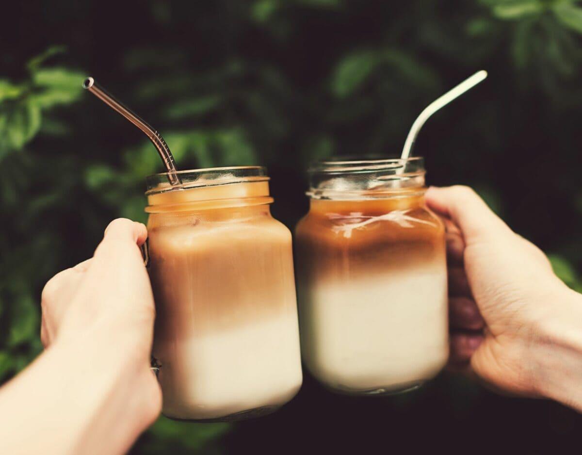 zwei hände halten eiskaffee mit koffein
