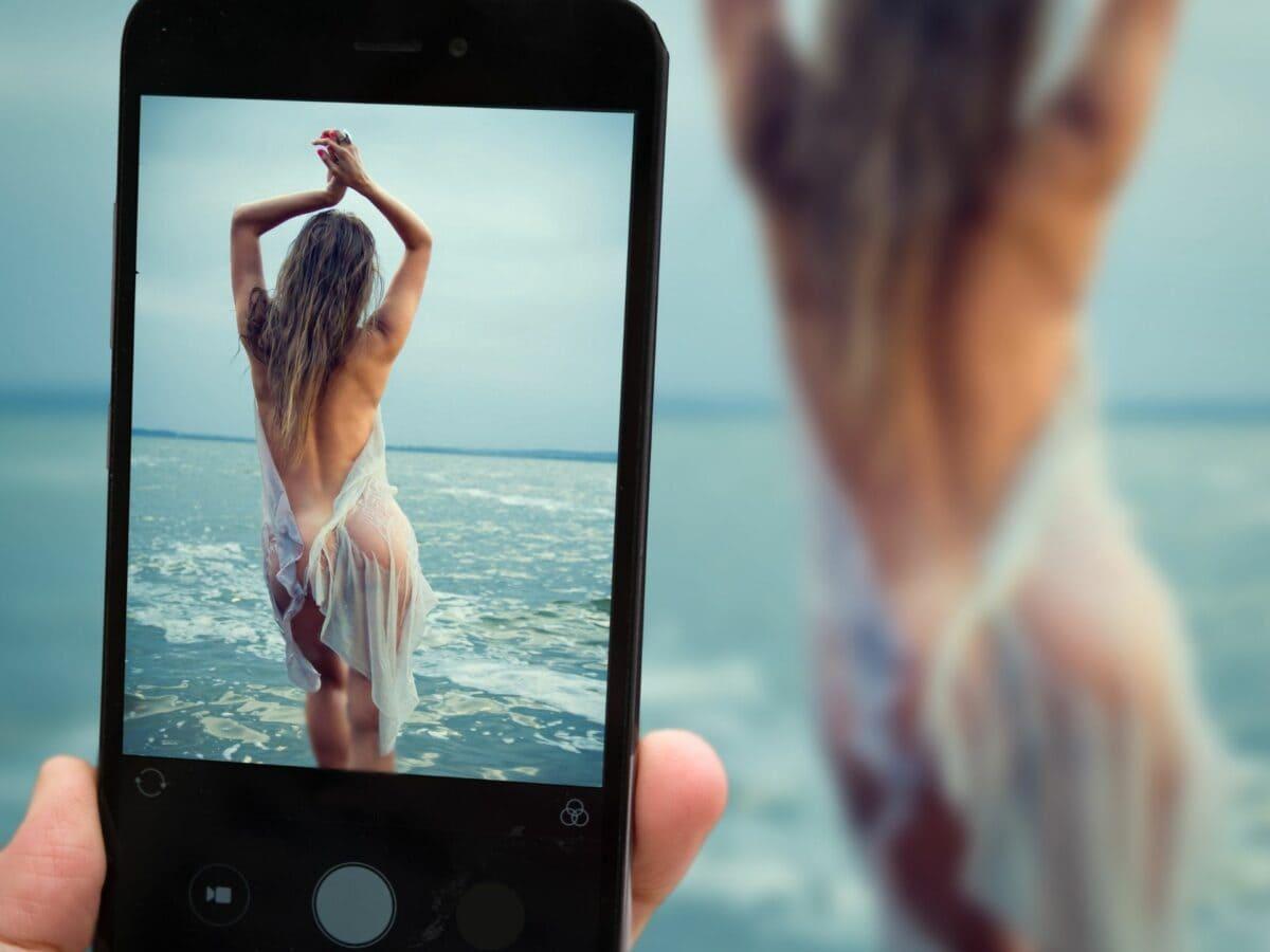 frau nackt am strand selfie mit smartphone